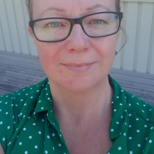 Petra Wallgren Björk. Woman wearing eye-glasses and a green blouse with white dots.